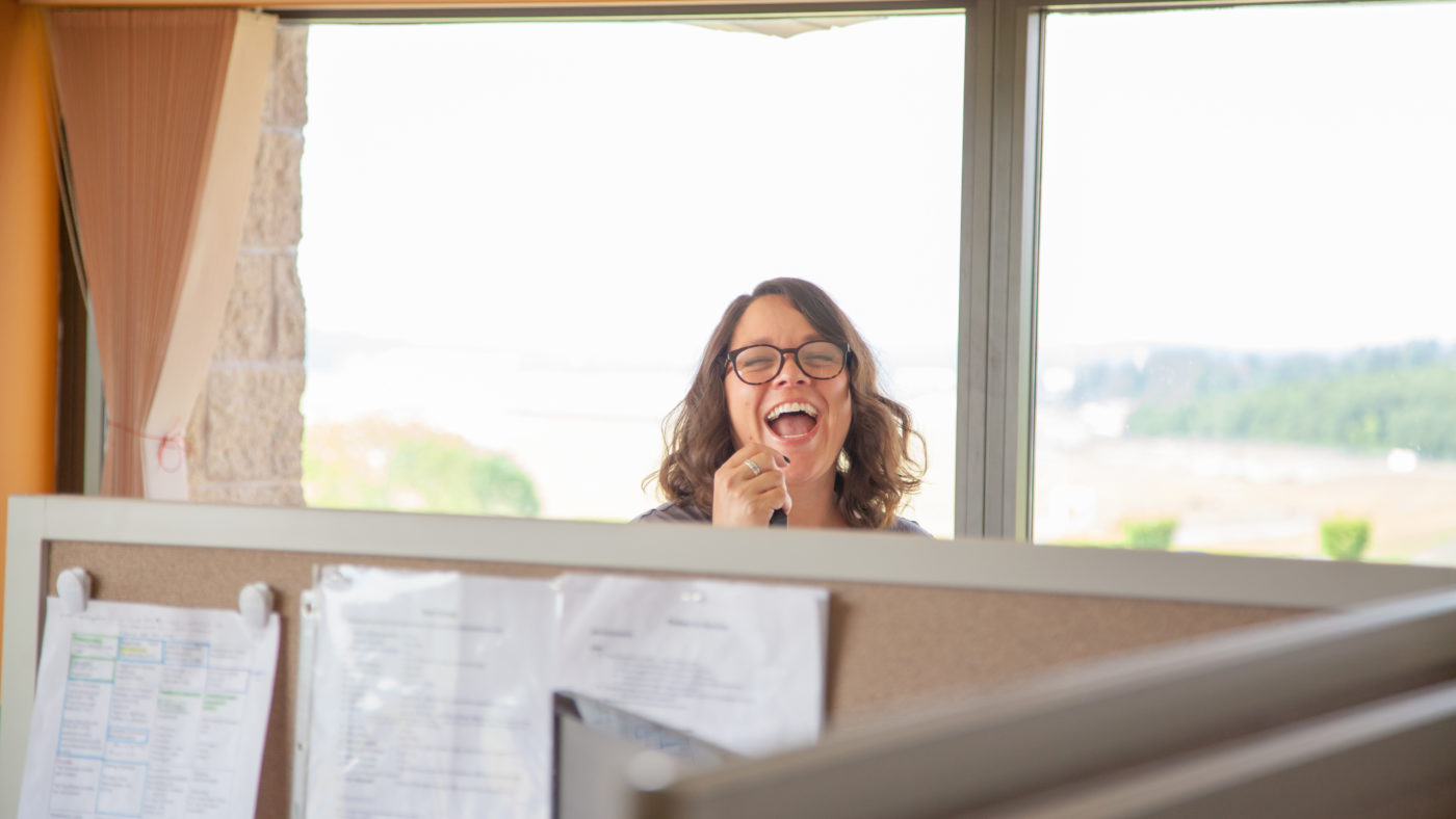 happy engaged employee peeks over cubicle wall