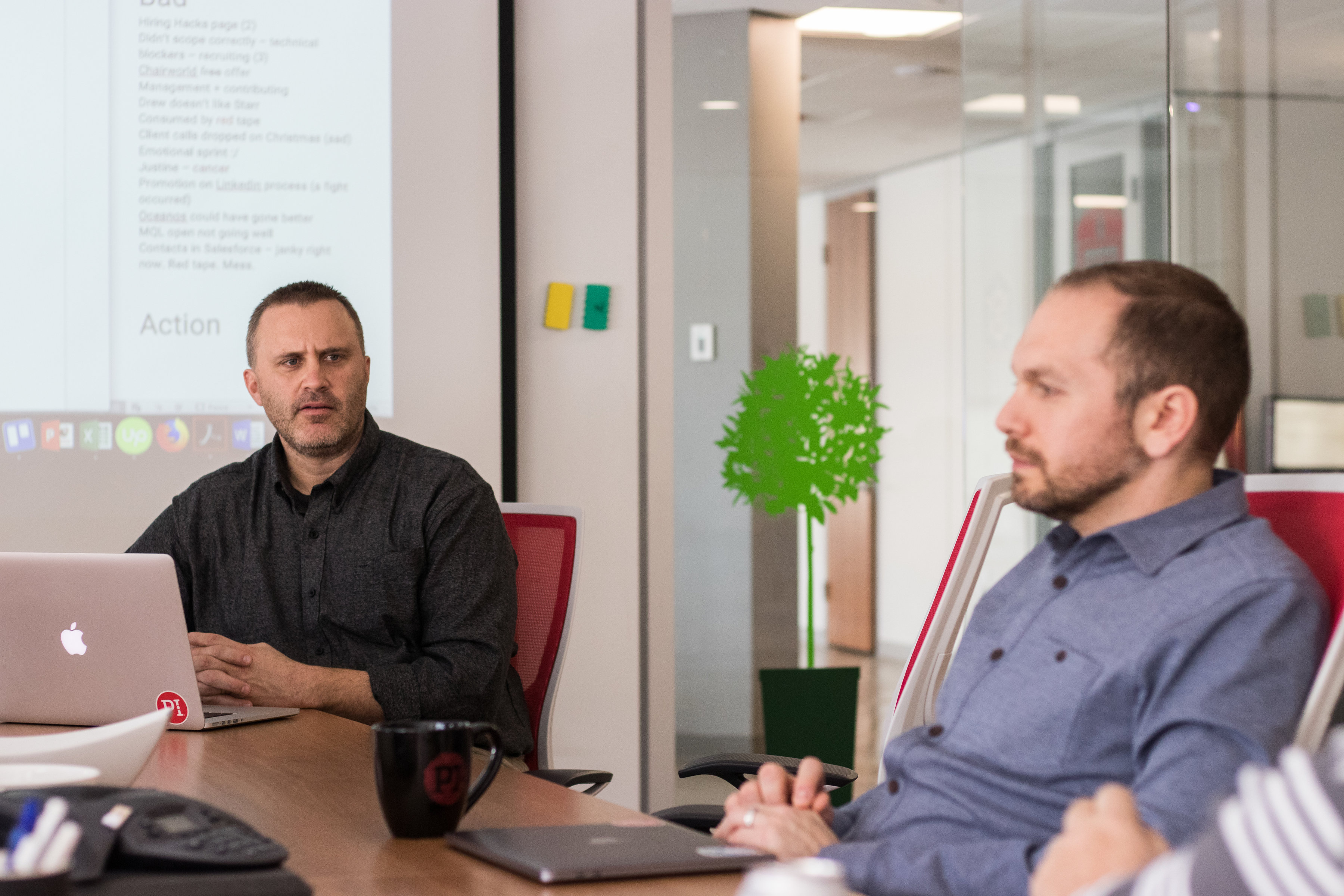 Two managers sit in a meeting room at an office