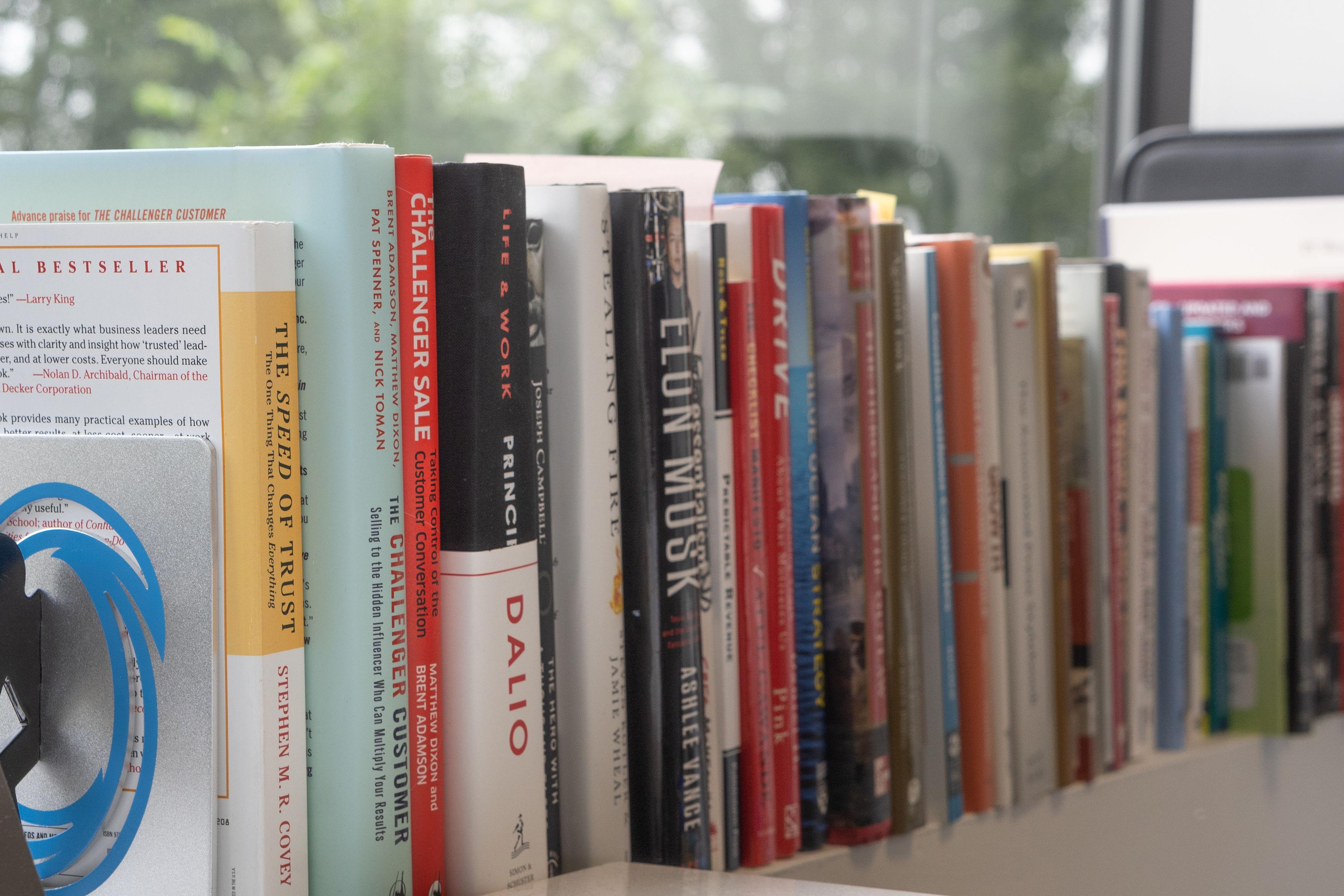 leadership books on a shelf in Drew's office