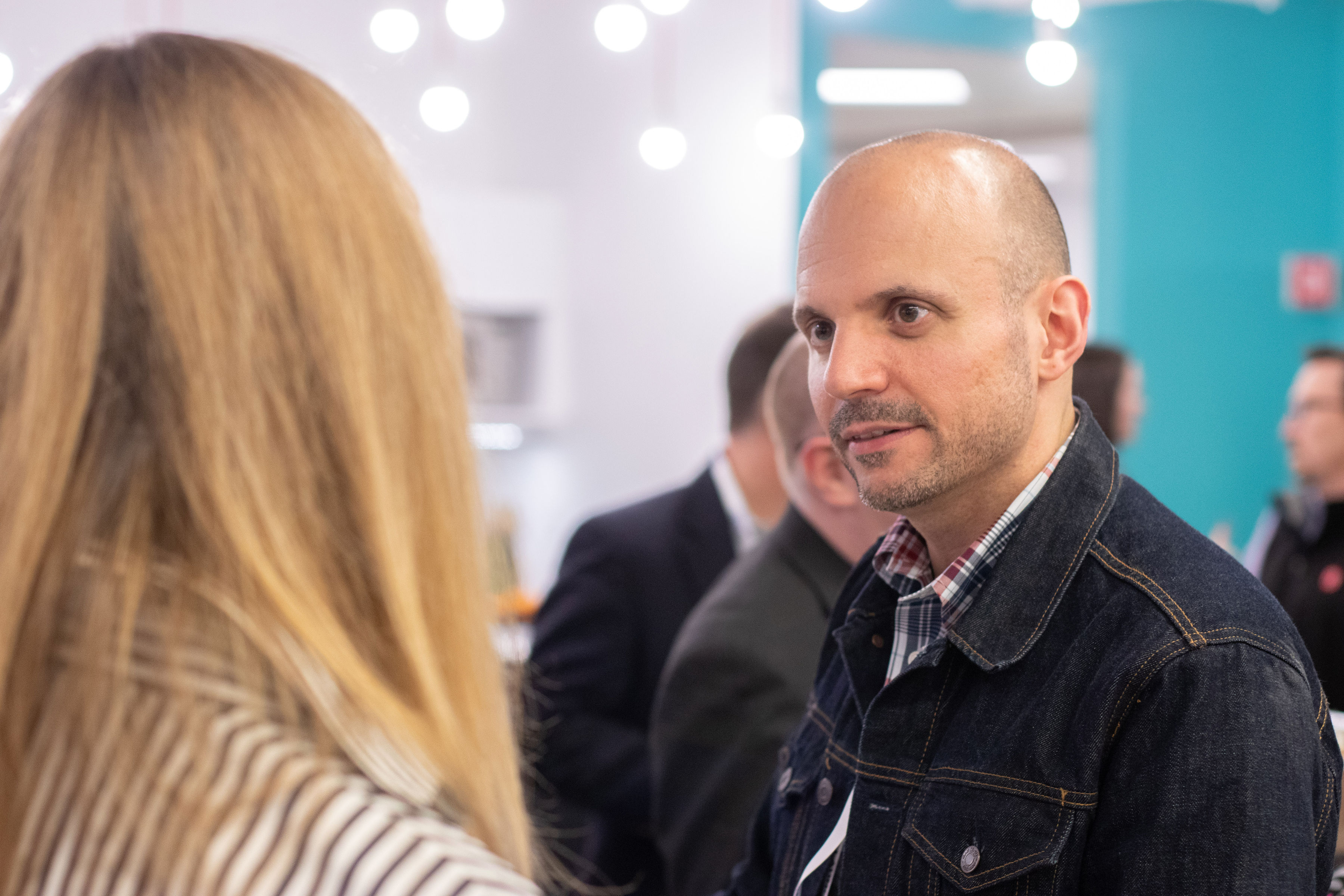 Two diverse employees talk at office event