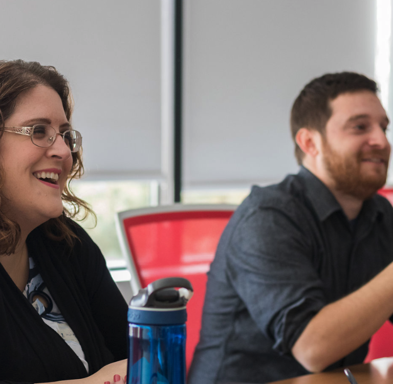 Two coworkers laughing in meeting