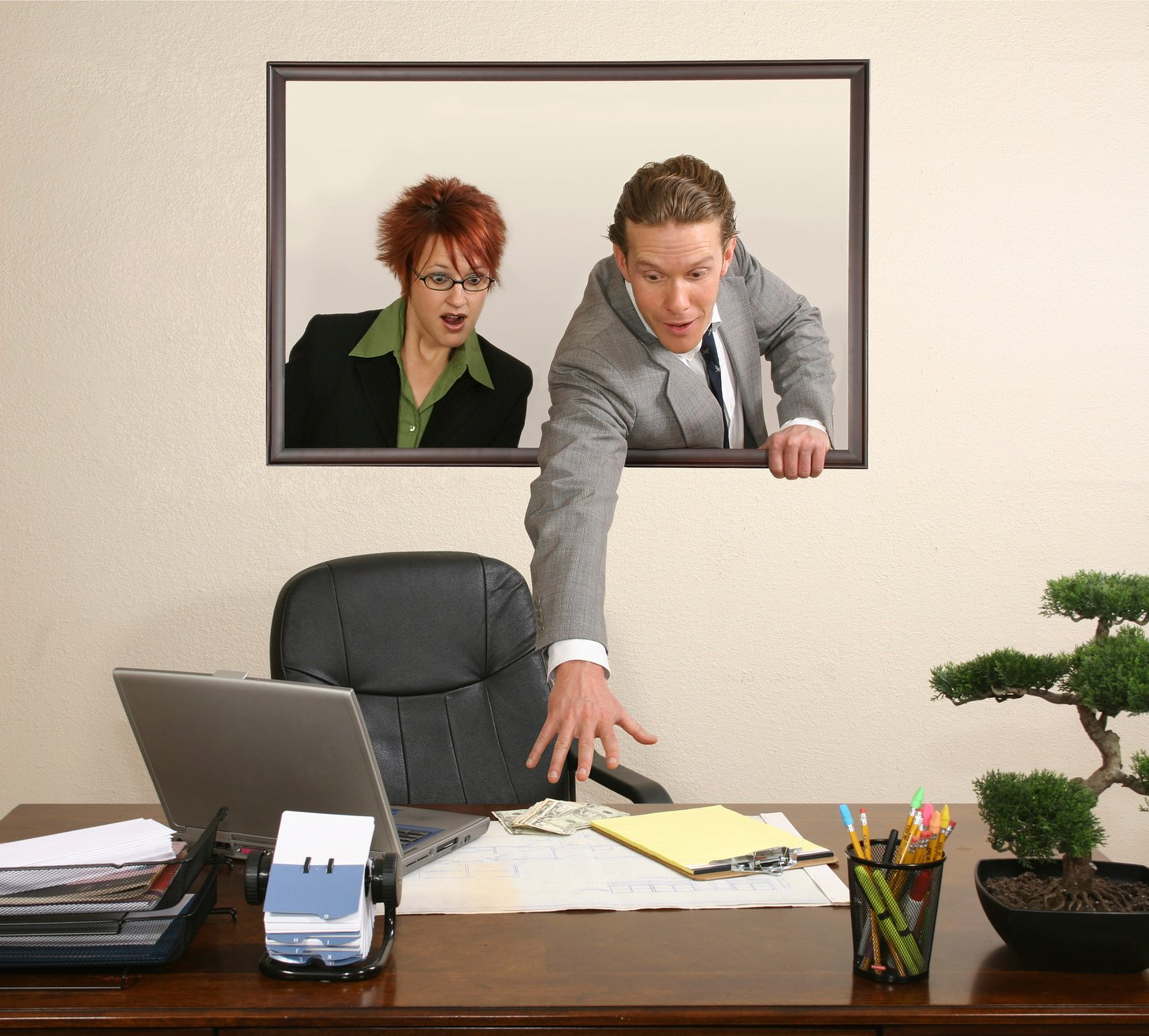 Two people reaching towards desk