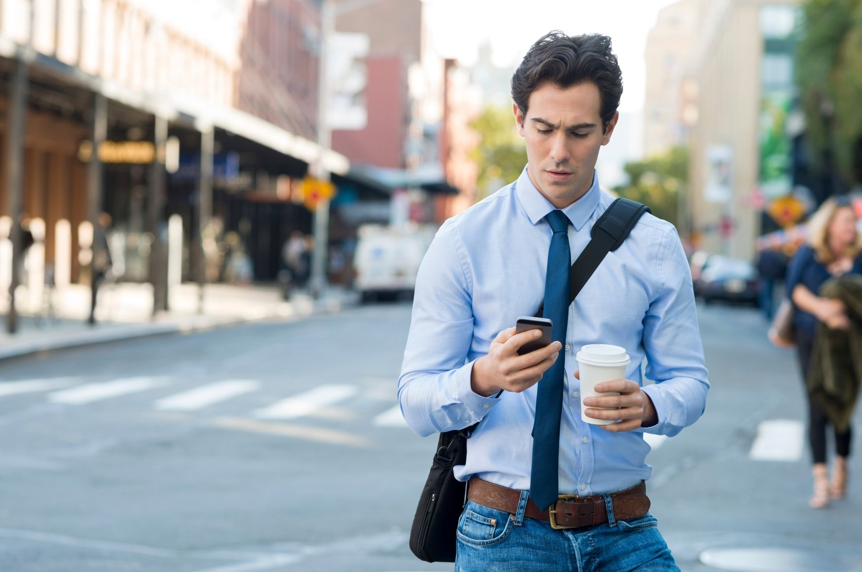 Man on phone holding coffee and walking through the streets