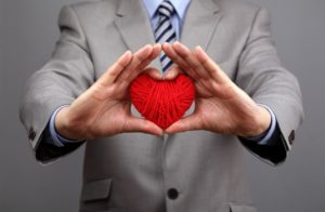 Man holding ball of yarn in the shape of a heart