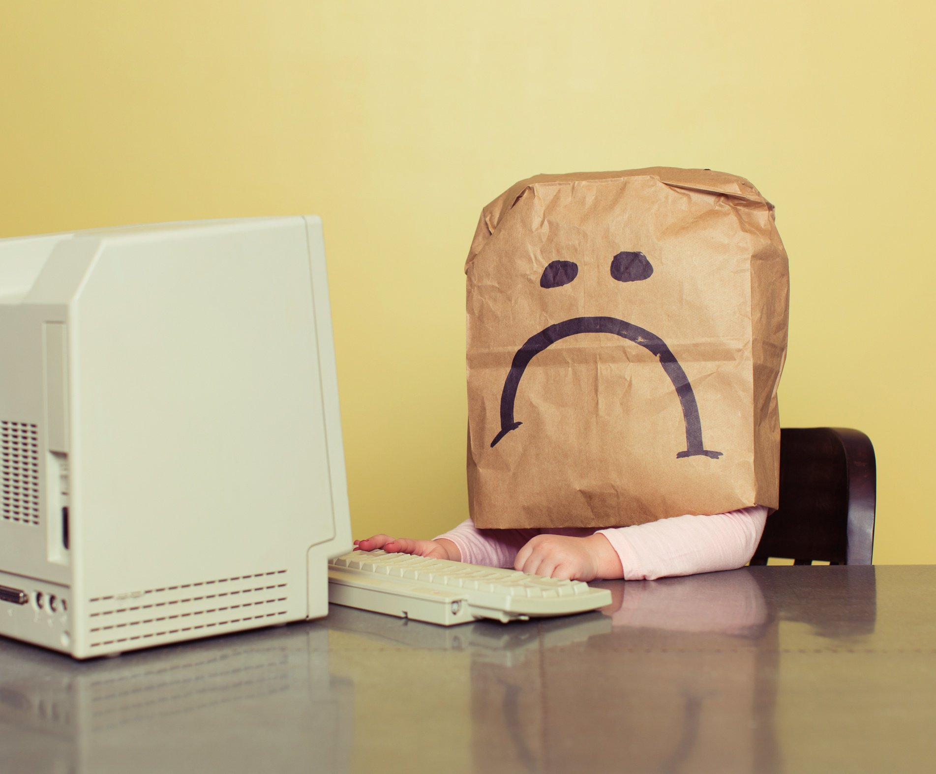 Employee with paper bag with sad face drawn on over their head