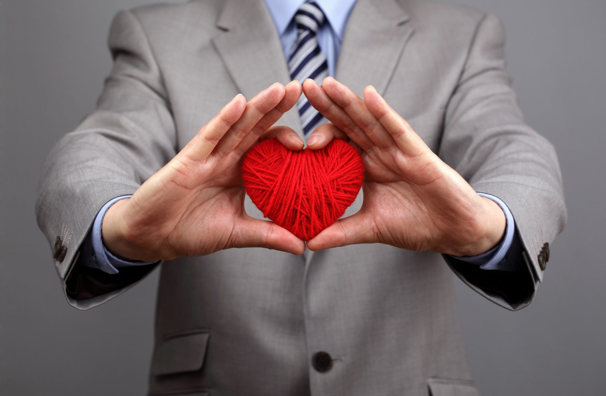 Man holding ball of yarn shaped as a heart