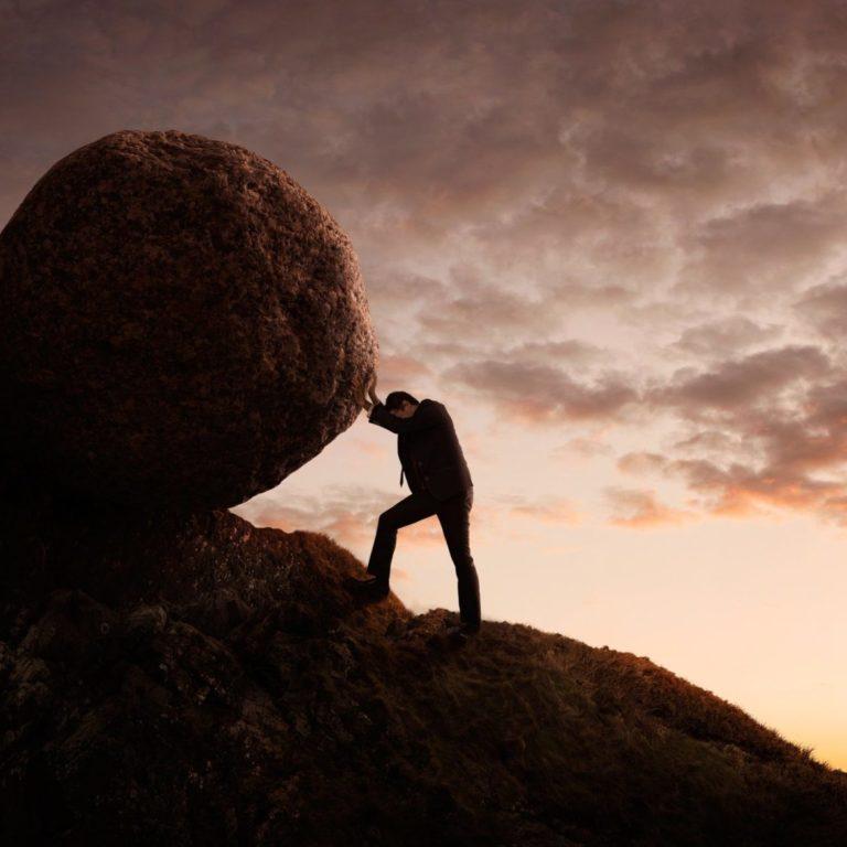 Man pushing boulder up mountain