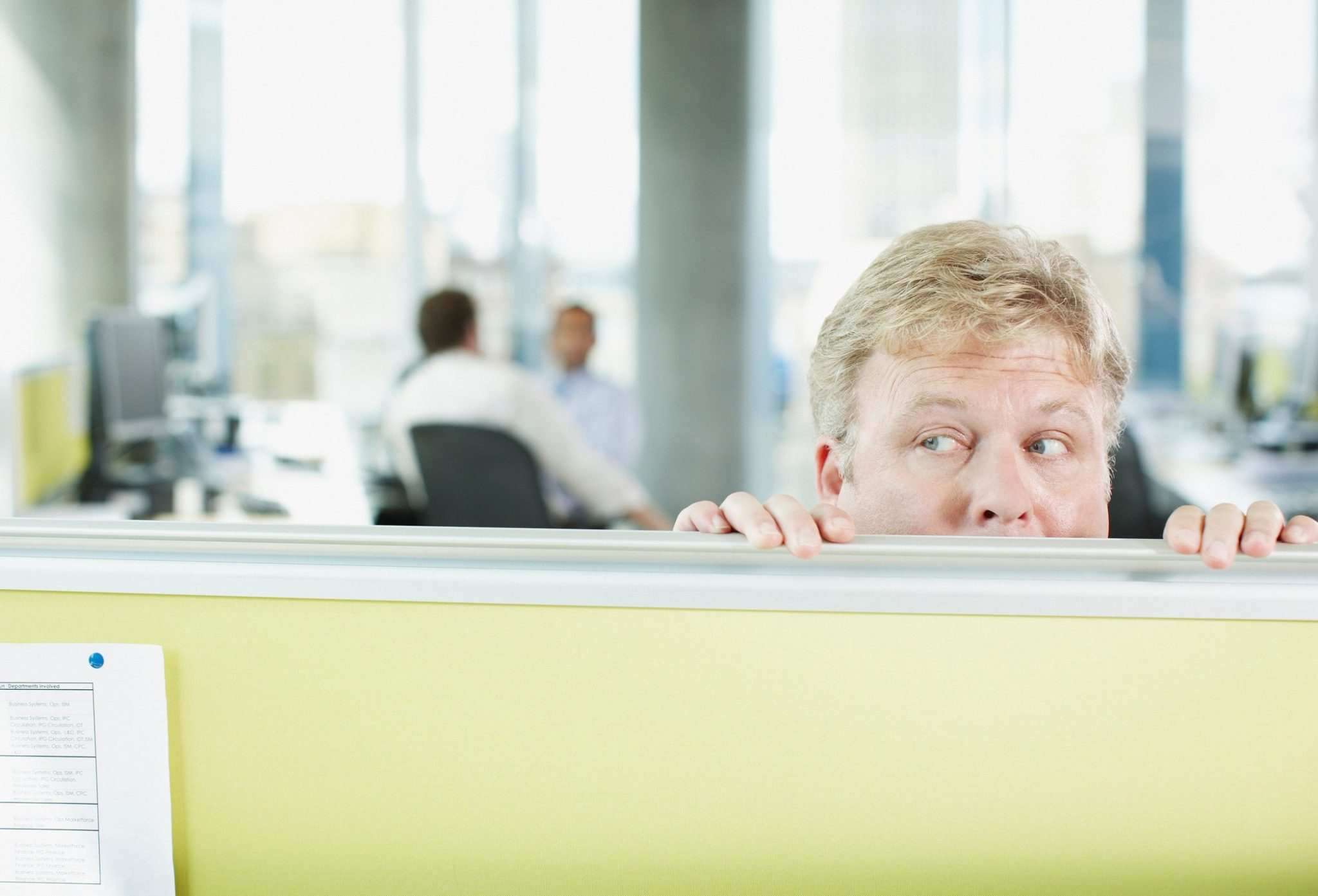 Man peering over desk