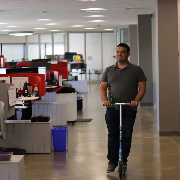 man on scooter in office