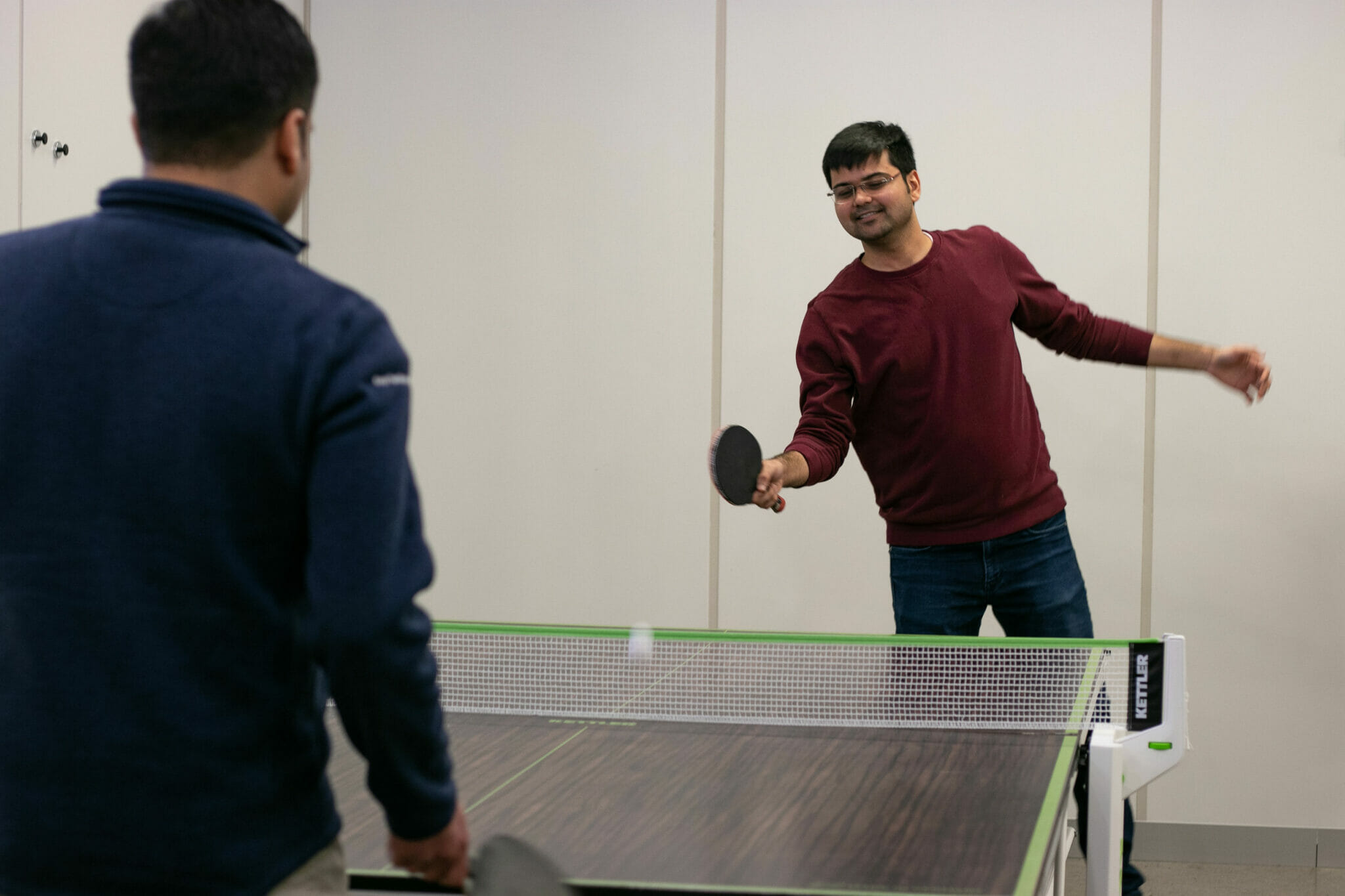 Employees playing ping pong in the office